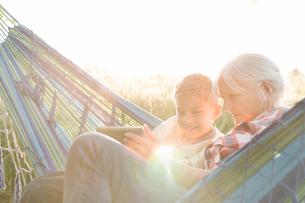 Grandmother and grandson using digital tablet in sunny hammockの写真素材 [FYI02698574]