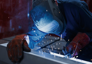 Welder using welding torch in steel factoryの写真素材 [FYI02698593]