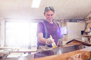 Male carpenter staining wood kayak in workshopの写真素材 [FYI02698597]
