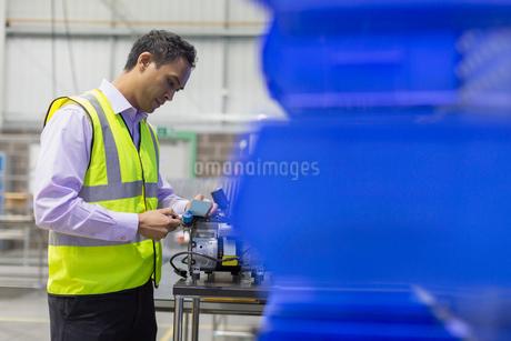 Manager examining part in steel factoryの写真素材 [FYI02698614]