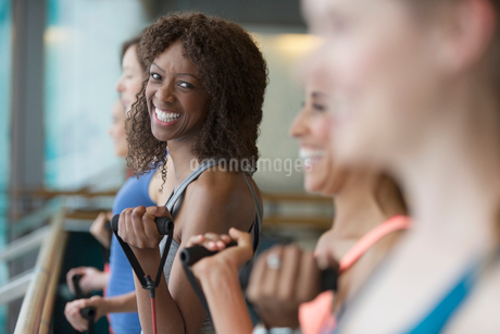 Portrait smiling woman exercising with resistance band in gym studioの写真素材 [FYI02698616]