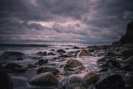 Large rocks on stormy, overcast nighttime beach, Bisserup, Denmarkの写真素材 [FYI02698640]