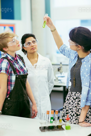 Teacher and students during chemistry lesson, wearing protective eyewear and looking at test tube wiの写真素材 [FYI02698678]