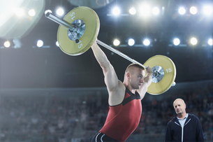 Coach watching male weightlifter squatting barbell overhead in arenaの写真素材 [FYI02698680]