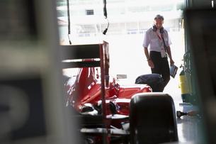 Manager examining formula one race car in repair garageの写真素材 [FYI02698690]