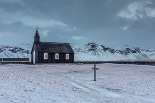 Church and graveyard in snowy remote mountain landscape, Budir, Snaefellsnes, Icelandの写真素材 [FYI02698718]