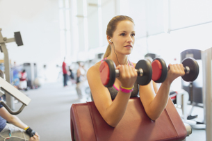 Woman doing dumbbell biceps curls at gymの写真素材 [FYI02698743]