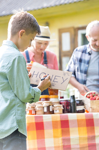 Boy drawing honey sign for farmer's market stallの写真素材 [FYI02698755]