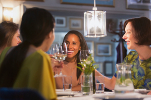 Smiling women friends toasting white wine glasses dining at restaurant tableの写真素材 [FYI02698760]