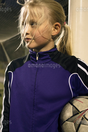 Girl holding soccer ball looking away while standing by goal postの写真素材 [FYI02698762]
