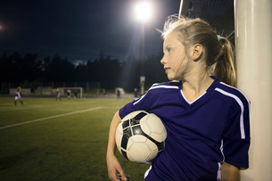 Girl holding soccer ball standing by goal post on fieldの写真素材 [FYI02698770]