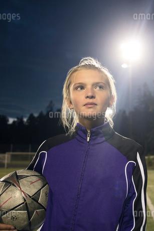 Girl holding soccer ball against sky at nightの写真素材 [FYI02698789]