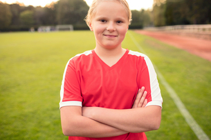 Portrait of happy athlete standing with arms crossed on soccer fieldの写真素材 [FYI02698863]