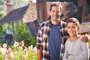Portrait smiling father and son in sunny flower gardenの写真素材 [FYI02698870]
