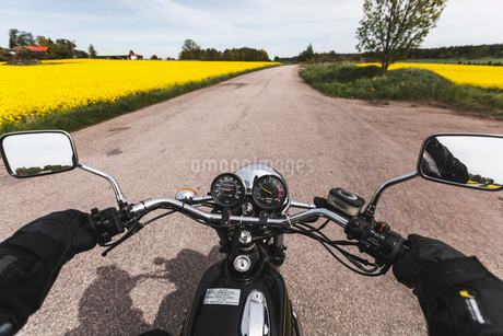 Cropped image of man riding motorcycle on roadの写真素材 [FYI02698899]