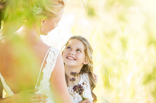 Smiling bridesmaid with flowers and bride during wedding reception in gardenの写真素材 [FYI02698927]