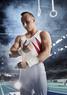 Male gymnast wrapping wrists below gymnastics rings in arenaの写真素材 [FYI02698958]