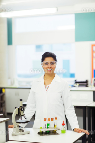 Portrait of smiling female teacher wearing protective eyewear, standing behind desk with microscopeの写真素材 [FYI02698989]