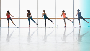 Women exercising at barre in exercise class gym studioの写真素材 [FYI02698997]