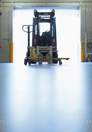Forklift parked in warehouse loading dock doorwayの写真素材 [FYI02699008]