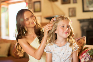 Bridesmaid helping girl with hairstyle in domestic roomの写真素材 [FYI02699019]