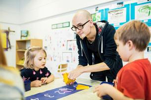 Male teacher assisting students in art class at kindergartenの写真素材 [FYI02699028]