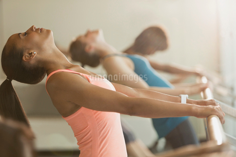 Women stretching in backbend at barre in exercise class gym studioの写真素材 [FYI02699034]
