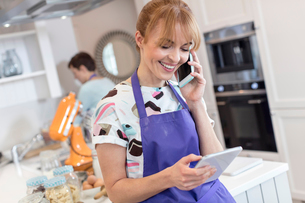 Smiling caterer working, talking on cell phone and using digital tablet in kitchenの写真素材 [FYI02699110]