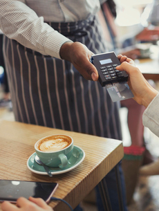 Customer paying waiter with credit card reader at cafe tableの写真素材 [FYI02699116]