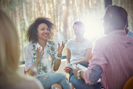 Smiling woman talking and gesturing in group therapy sessionの写真素材 [FYI02699119]