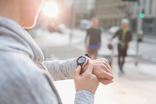Female runner checking smart watch on urban streetの写真素材 [FYI02699120]
