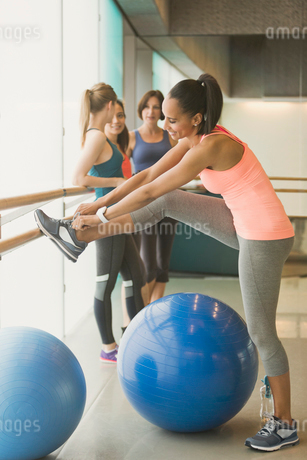 Woman tying shoe at barre in exercise class gym studioの写真素材 [FYI02699123]