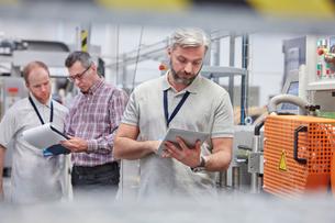 Male supervisor using digital tablet in fiber optics factoryの写真素材 [FYI02699128]