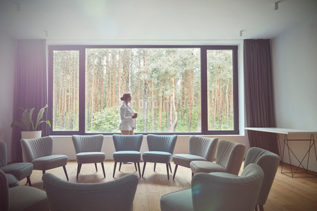 Pensive woman looking out windows at tress in group therapy roomの写真素材 [FYI02699138]
