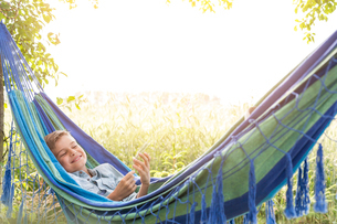 Carefree boy listening to music on mp3 player in rural hammockの写真素材 [FYI02699147]