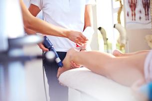Masseuse applying gel to woman's leg in preparation for ultrasound probeの写真素材 [FYI02699185]