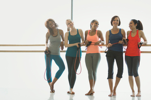 Portrait smiling women with resistance bands at barre in exercise class gym studioの写真素材 [FYI02699190]