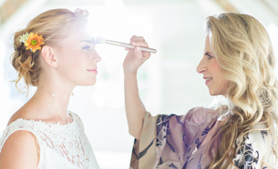 Matron of honor checking bride's make up before wedding ceremonyの写真素材 [FYI02699198]