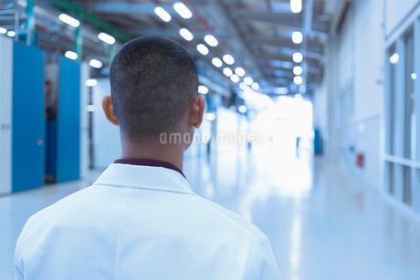 Scientist looking down long factory corridorの写真素材 [FYI02699215]