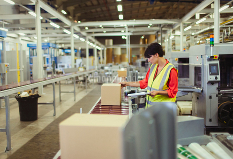 Worker checking cardboard boxes on conveyor belt production line in factoryの写真素材 [FYI02699222]