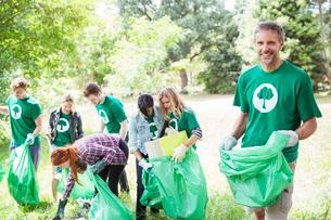 Portrait of smiling environmentalist volunteer picking up trashの写真素材 [FYI02699250]