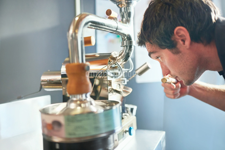 Male coffee roaster smelling, testing coffeeの写真素材 [FYI02699256]