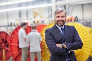 Portrait smiling, confident businessman in fiber optics factoryの写真素材 [FYI02699263]