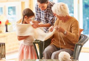 Grandmother knitting scarf around granddaughterの写真素材 [FYI02699297]