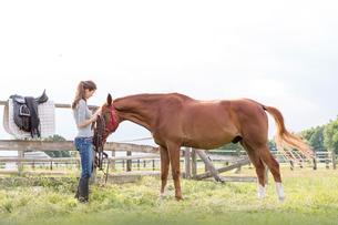 Woman preparing horse for horseback riding in rural pastureの写真素材 [FYI02699307]