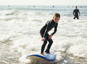 Full length of boy surfing in sea with father in backgroundの写真素材 [FYI02699337]