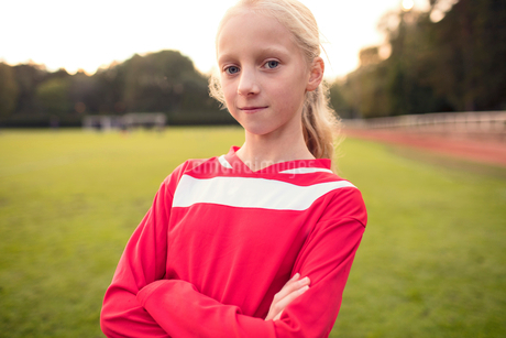Portrait of confident girl standing with crossed arms at soccer fieldの写真素材 [FYI02699343]