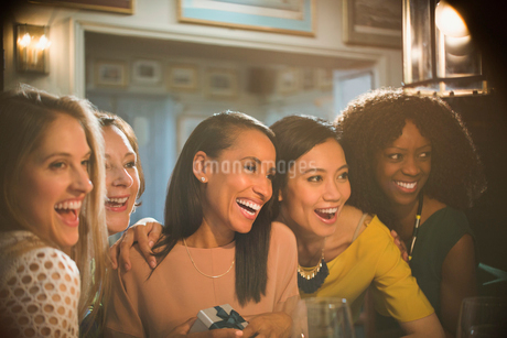 Smiling women friends celebrating birthday in restaurantの写真素材 [FYI02699413]