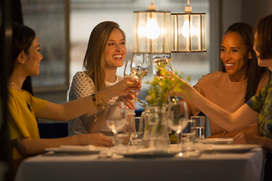 Smiling women friends toasting white wine glasses dining at restaurant tableの写真素材 [FYI02699437]