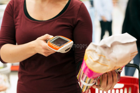 Midsection of woman scanning product with bar code reader in supermarketの写真素材 [FYI02699442]